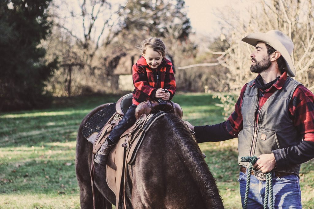 small-boy-horse-back-riding-dad-walking-next-in-plaid